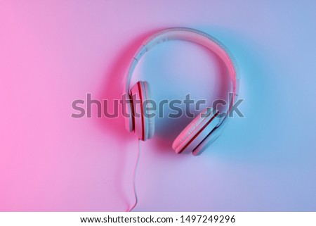 Classic wired headphones with gradient blue pink neon light. Retro style.Retro wave. 80s. Minimalistic music concept. Top view #1497249296