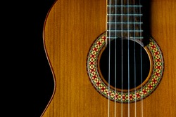 classical, acoustic guitar front closeup, strings, sound hole and soundboard, dark background, copy space, top view