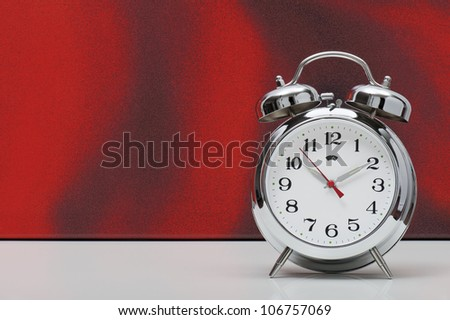 classical alarm clock on red background