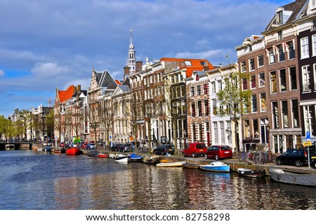 Classical Amsterdam view. Boat floats on the channel on the background of Dutch houses. Urban scene.