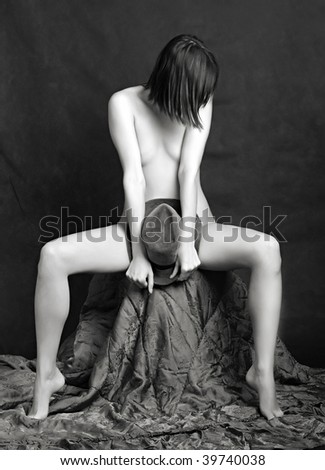 Classical artistic nudity style picture of woman sitting on black background