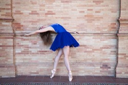classical ballet dancer with turkey blue tutu doing different poses and postures on a background of red bricks. Classical ballet concept.