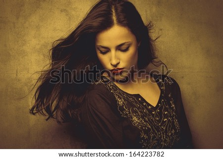 classical beauty young long hair brunette woman in embroidered shirt in golden tones