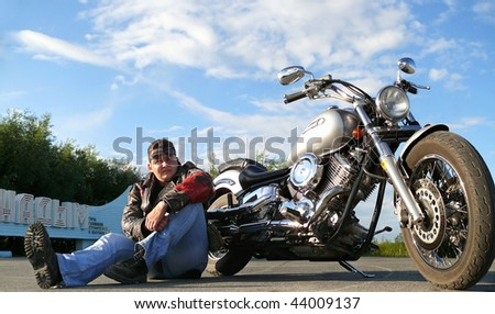 Classical biker Klimenko Oleg in black spectacles sits near his chopper. Nadym, Russia. - stock photo