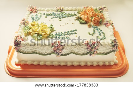Classical birthday cake design with a lot of flowers of cream.