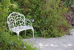 Classical decorative white wrought iron garden bench at the side of a path and flower borders