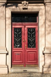 Classical European doorway with stone pillars around red door with gold details. Ornate details in dark windows and stone figurine over entrance. Shot in bright daylight