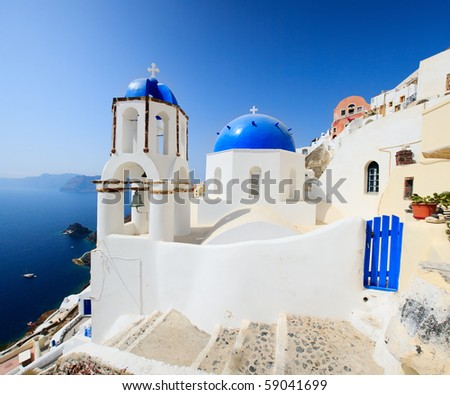 Classical greek style church in traditional white and blue Oia village in Santorini