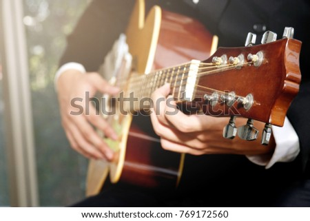 Classical guitar performance : Close up of a male musician sitting in a classical guitar playing a song.   #769172560