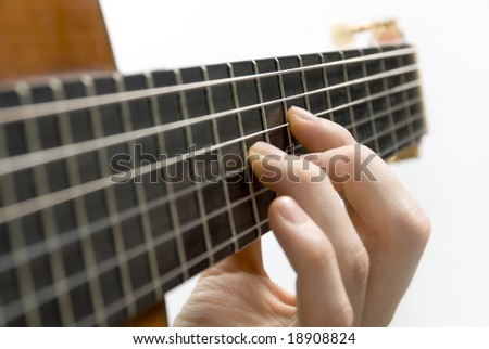 Classical guitar's fingerboard with playing hand and white background