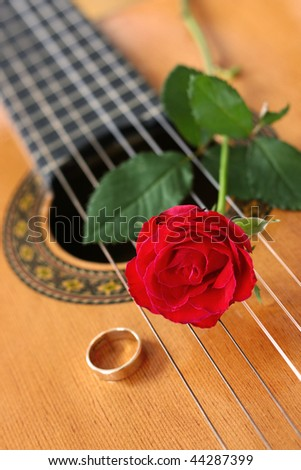 Classical guitar with a red rose and gold ring