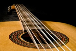 Classical guitar with vibrating strings on a black background