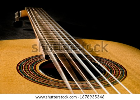 Photo of  Classical guitar with vibrating strings on a black background