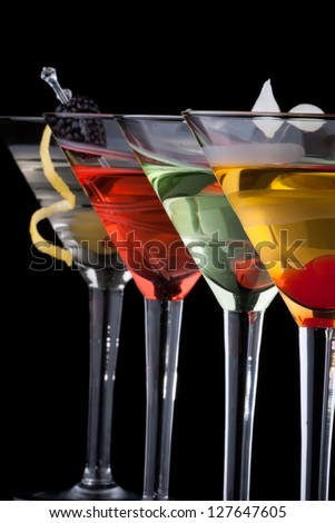 Classical martini in chilled glass over black background on reflection surface, garnished with freah blackberry, maraschino cherry, marinated pearl onoions, olive and lemon twist.