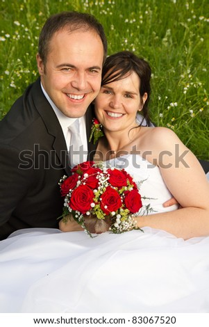 classical newly wed couple with wedding gown dark suit and red bridal bouquet the groom holding his bride on a meadow