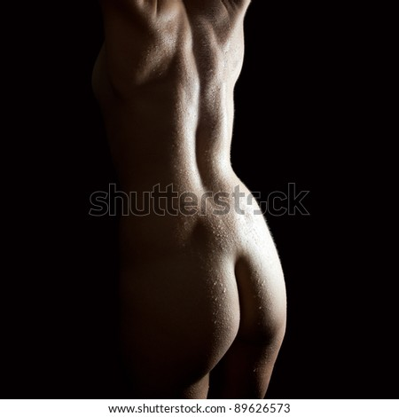 Classical nude of a beautiful young woman with wet body, closeup of her back in front of black background
