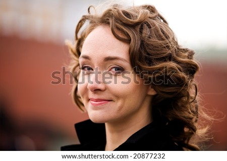 Classical portrait of attractive smiling woman outdoors