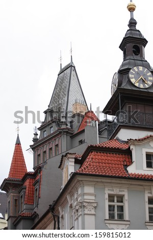 Classical Prague architecture. Gray gothic house with red tiling roof and clock tower, Czech Republic