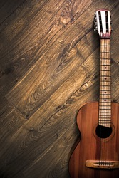 Classical six-string guitar on a wooden surface; Dark photo, rustic (Vertical position)