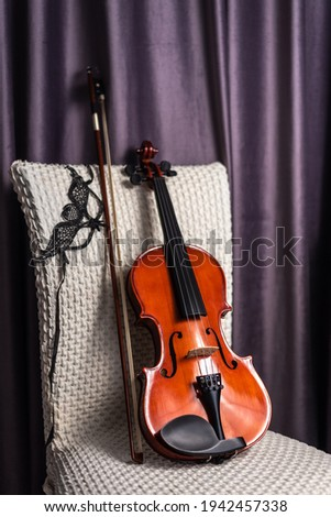 Classical wooden musical string instrument and carnival mask on beige chair. Intermission rest time in room. Pause on live concert. Music, melody, artistry and inspiration concept Stock photo ©