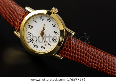 Classical wrist watch on black background.