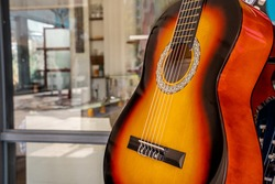 classical yellow six-string guitar on shop window background