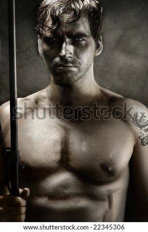Classically stylized portrait of a shirtless young man portraying tribal warrior holding spear