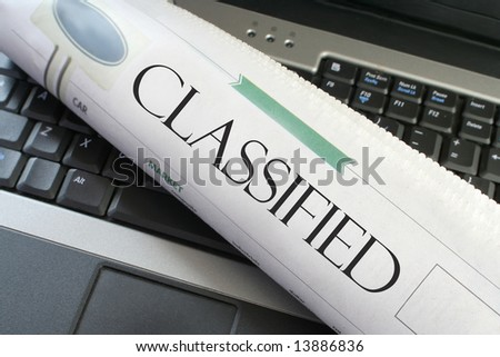 classified headline section of the newspaper on a laptop computer