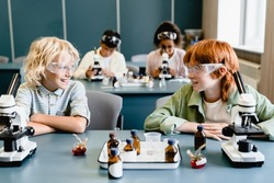 Classmates kids schoolchildren making experiments listening to the chemistry science class lesson at school lab wearing protective eyeglasses using reagents.