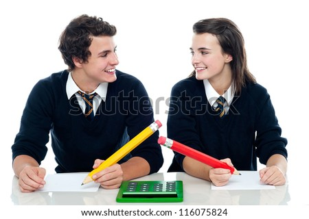 Classmates looking at each other and discussing the correct answer before writing