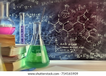 Classroom desk and drawn blackboard of chemistry teaching with books and instruments. Chemical sciences education concept. Horizontal composition. Front view