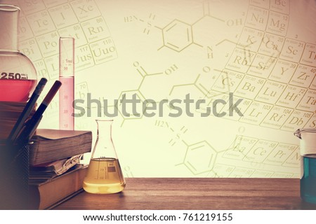 Classroom desk of chemistry teaching with books and instruments. Chemical sciences education concept. Horizontal composition. Front view #761219155