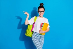 Classroom number one here. Positive college student girl hold books rucksack point finger copyspace demonstrate courses ads promo wear white denim isolated bright shine color background
