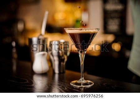 classy bartender garnish martini espresso cocktail drink foam coffee bean on top bar counter #695976256