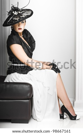 Classy lady in elegant haute couture ensemble with a fascinator hat and accessories sitting demurely on a seat with erect posture
