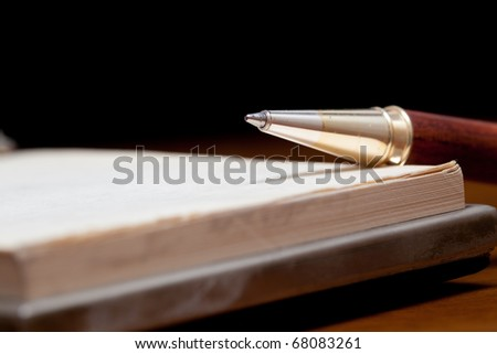 Classy pen lying on a notebook against a black background