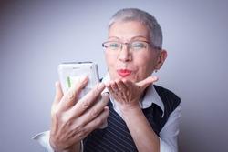 Classy senior woman sending kisses over social media to her family and relatives
