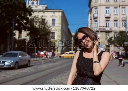 Classy smiling model wearing fashionable dress and glasses walking on the city streets. Space for text