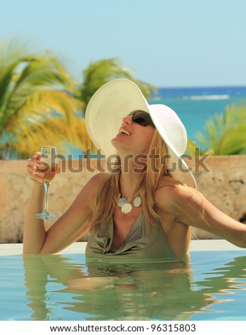classy woman in a private pool with a glass of champagne