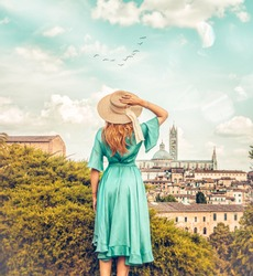 classy woman standing with the back in bohemian background in front of old city landscape, big hat and green dress romantic lifestyle looking in the distance