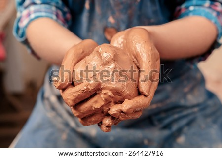 Clay ball. Close-up of female hands holding a ball made of clay to start working on the wheel