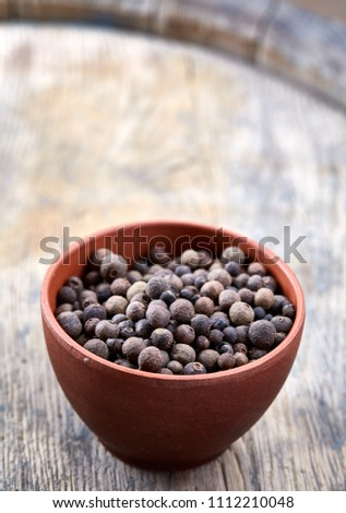 Clay bowl with dried allspice berries on wooden barrel, top view, close-up, macro, selective focus, vertical. #1112210048