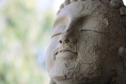 Clay Buddha head. With cracks and worn effect by rain and atmospheric events.