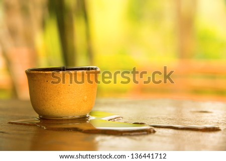 clay cup full with water overflow on table