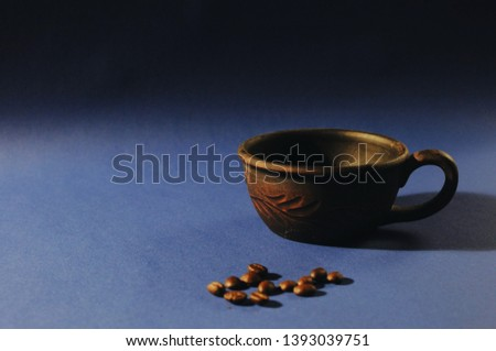 Clay cup with coffee beans on blue background