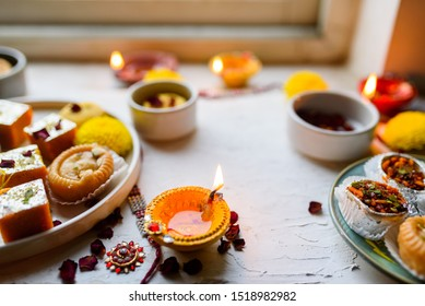 Stock photo of clay diyas or lamp spread with Diwali  or Divali or Deepawali sweets or mithai and flowers lit for festival