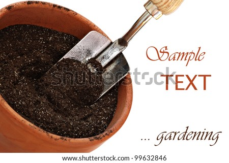 Clay flower pot with potting soil and spade on white background with copy space.