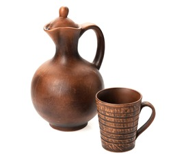 Clay jug with a mug - typical handmade products on a white background isolated