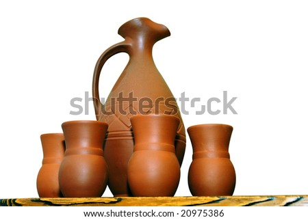 Clay jugs and cups on a shelf isolated on white