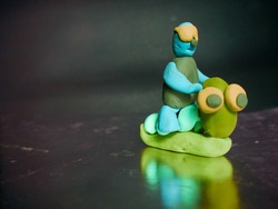 Clay man seating upon cartoon creature isolate on grey frame